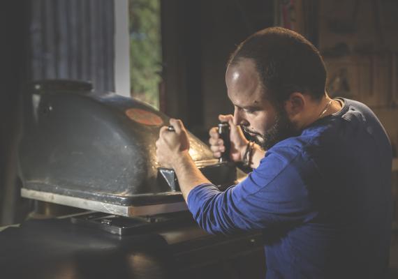 Damien Béal dans son atelier de menuiserie, geste de l'artisan, découpe du cuir